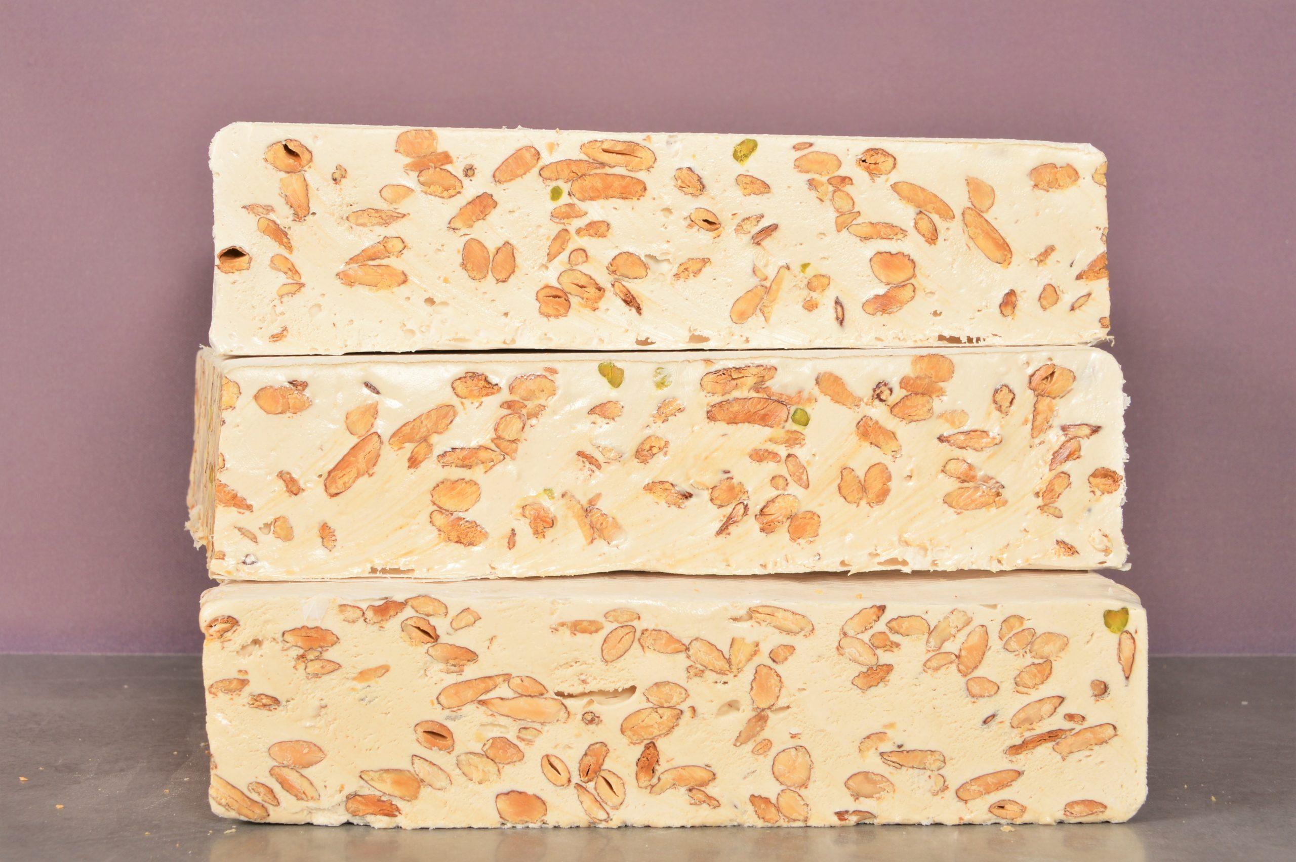 Vente en ligne - Nougat artisanal - Photo de trois nougats présenté l'un sur l'autre - prix du nougat au kilo